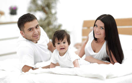 Portrait of happy young family lying in bed together