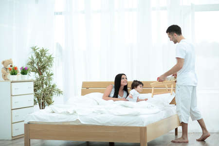 Family having nutritive breakfast in bed in the morning Stock Photo