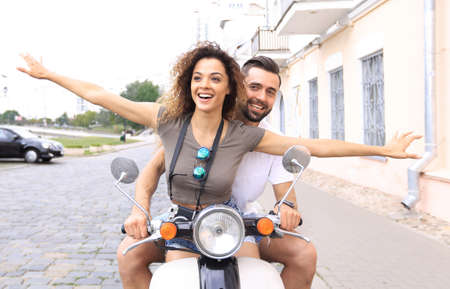 Beautiful young couple is smiling while riding a scooter