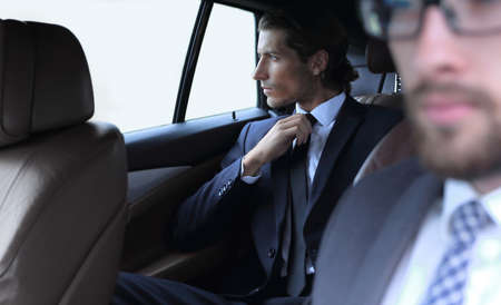 business people sitting in car