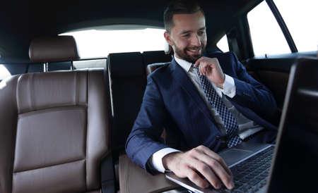 businessman reads information on laptop while sitting in car Foto de archivo