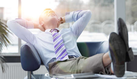 Young businessman leaning back in his chair Stock Photo