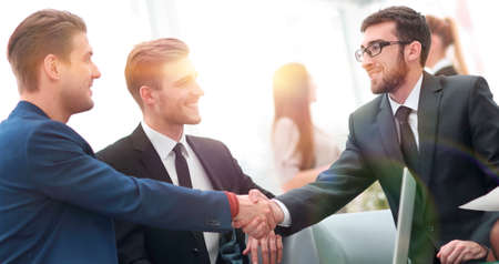 Partners concluding deal and shaking hands in the presence of team members Stock Photo