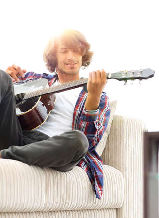 Handsome man playing on the guitar on the couch at home