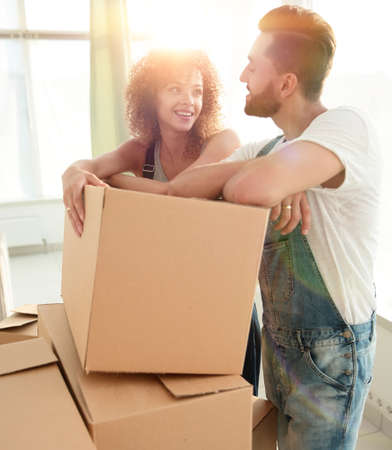 Happy couple standing near boxes in their new apartment.