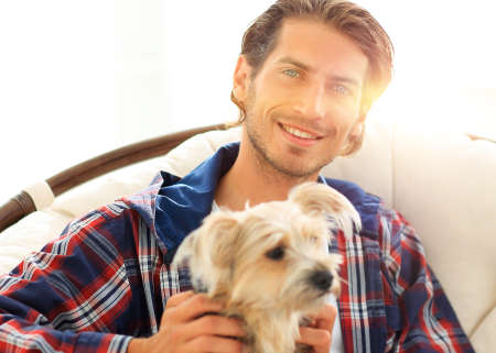 close-up of a smiling guy stroking his dog while sitting in a large armchair. Foto de archivo