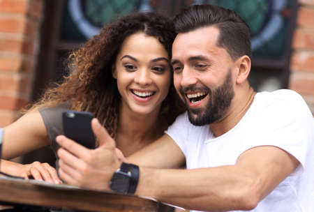 Portrait of a young  couple sitting down at a cafe terrace Stock Photo