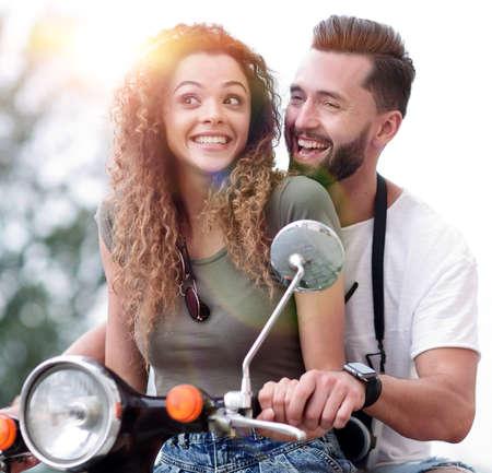 Couple attrayant sur un scooter sur une journée ensoleillée dans la ville
