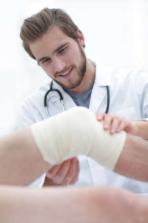 closeup of a doctor examining injured leg of the patient Stock Photo