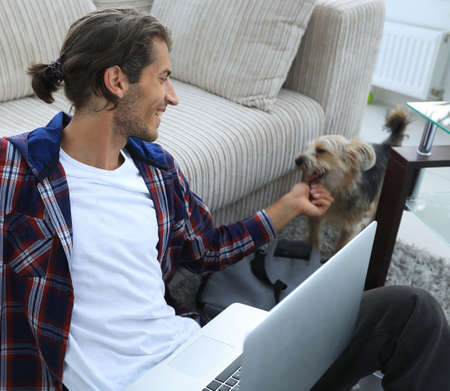 stylish young man stroking his pet and working on laptop 스톡 콘텐츠