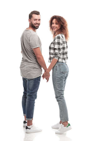 Rear view of happy couple holding hands and looking at camera