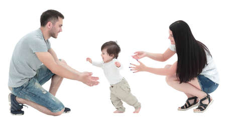 little boy making  first steps with the help of parents