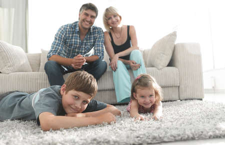 Portrait of happy family sitting together in living room 版權商用圖片 - 99163348