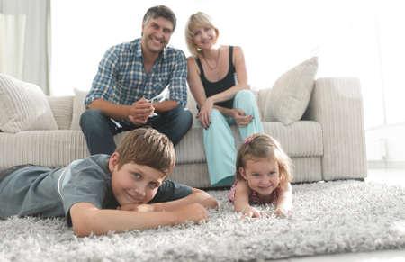 Portret van gelukkige familiezitting samen in woonkamer