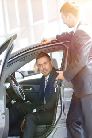 successful businessman, receiving the keys to the car from the seller in the showroom Stock Photo - 99478585