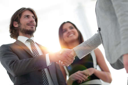 Businesspeople  shaking hands against room with large window loo Standard-Bild