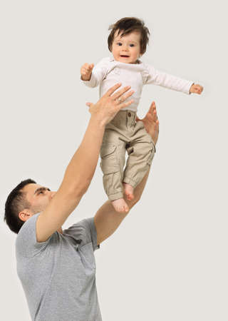 Father throws his laughing son in the air Foto de archivo