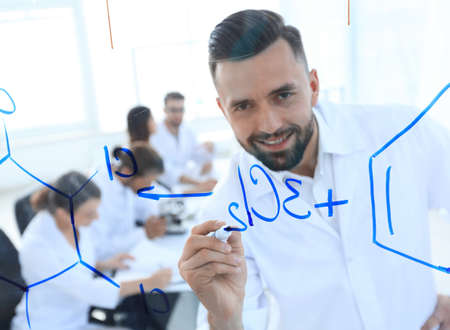 close up of a smiling scientist writes a formula on the blackboard Stock Photo