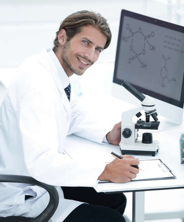 Laboratory worker sitting by table with microscope
