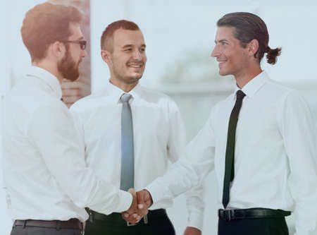 friendly handshake colleagues at a meeting