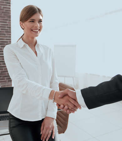 woman Manager welcomes the client with a handshake. Banco de Imagens