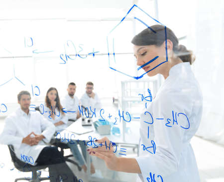 view through the transparent Board. female biochemist makes a report to colleagues Stock Photo
