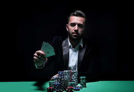 Happy poker player winning and holding a pair of aces Stock Photo