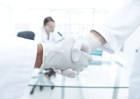Doctors in lab coats greeting each other with handshake Stock Photo