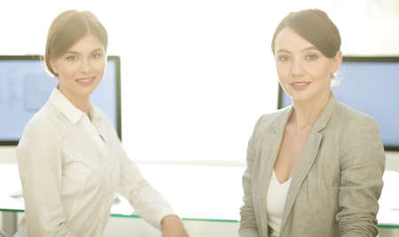 portrait of two business women on the background of the workplace. Stockfoto