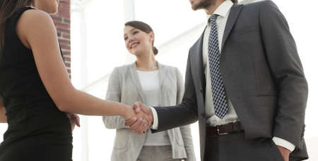 Businesspeople  shaking hands against room with large window loo Stock Photo