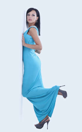 young slender woman in blue long dress posing on white background