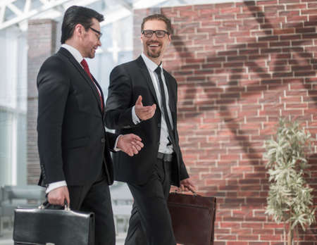 two smiling businessman walking in the office hall
