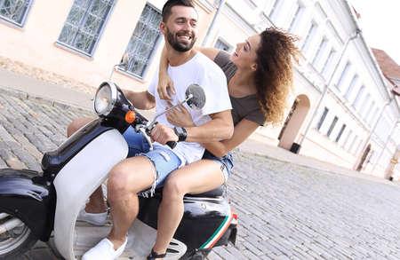 Vista lateral de longitud completa de la feliz pareja montando en moto retro