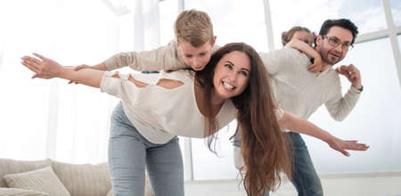 happy parents play with their children in the spacious living room Banque d'images
