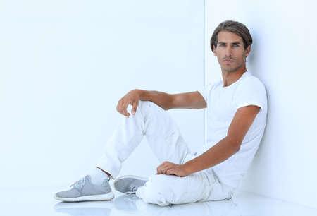 pensive boy sitting near the wall Stock Photo