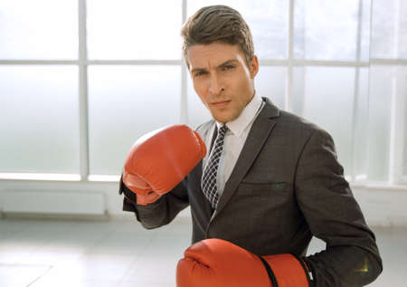 purposeful young businessman in Boxing gloves.