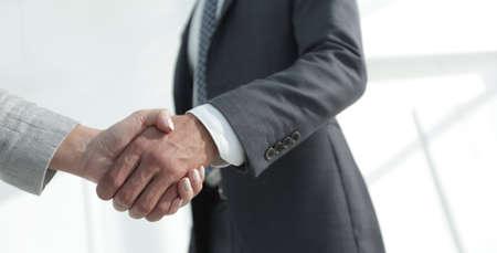 Excited smiling businessman handshaking partner at meeting, Foto de archivo