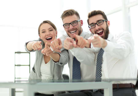 close up.a smiling business team pointing at you