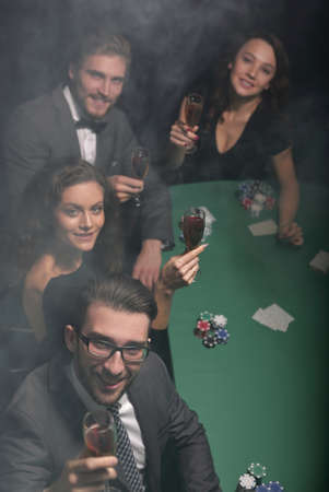 Group of young rich people is playing poker in the casino Stok Fotoğraf