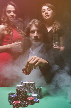 fortunate gambler surrounded by seductive elegant women Reklamní fotografie