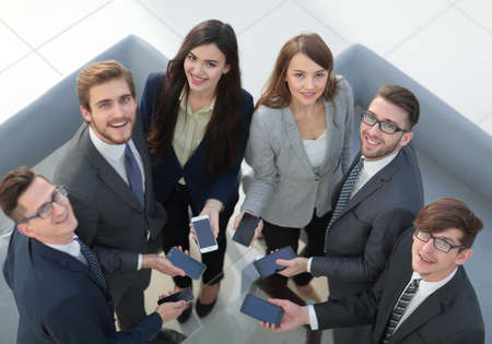 Group of  business colleagues using mobile phones in  the office