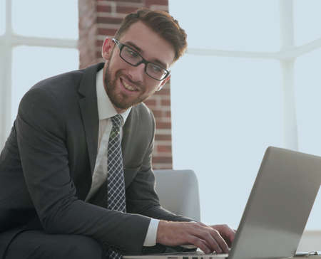 businessman with glasses is sitting at the desk in the office Stock Photo