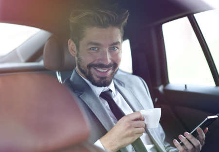 Businessman drinking coffee in car with phone in hand Imagens