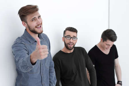 casual men next to the wall showing thumbs up