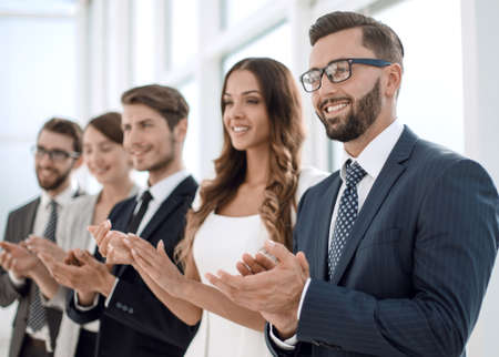 group of business people applauding someone standing in the offi