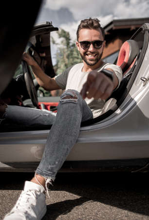 close up.fashionable young man sitting in a convertible and poin