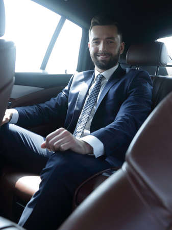 businessman sitting in the back seat of a car Фото со стока