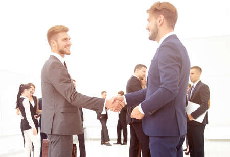 handshake of business partners on the background of business team