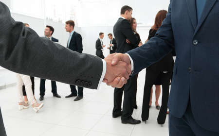 closeup of handshake of business partners on the background of business team