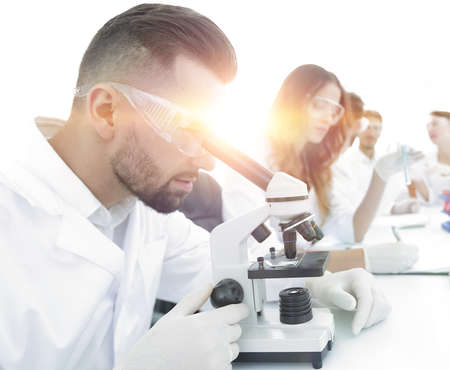 male lab technician looks at the sample under a microscope 写真素材